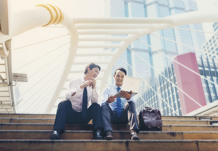 Business People Discussing Over Laptop While Sitting On Staircase