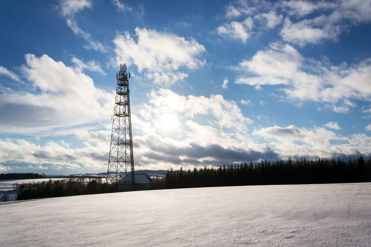 Communications tower on field against sky during winter