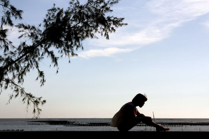 People sit on the short wall beside the sea and tree. ASIA Alone Asian  Silhouette Sit Taiwan Travel Wall Woman Beside Girl Horizon Over Water Ocean One Person People person Real People Sea Sea And Sky Short Silhouette Tranquil Scene Tranquility Tree Water