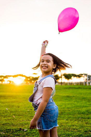 Side view portrait of smiling girl holding balloon while standing at park during sunset
