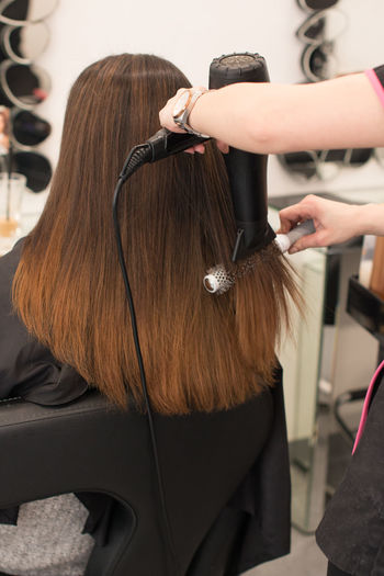 Cropped hands of hairdresser drying woman hair