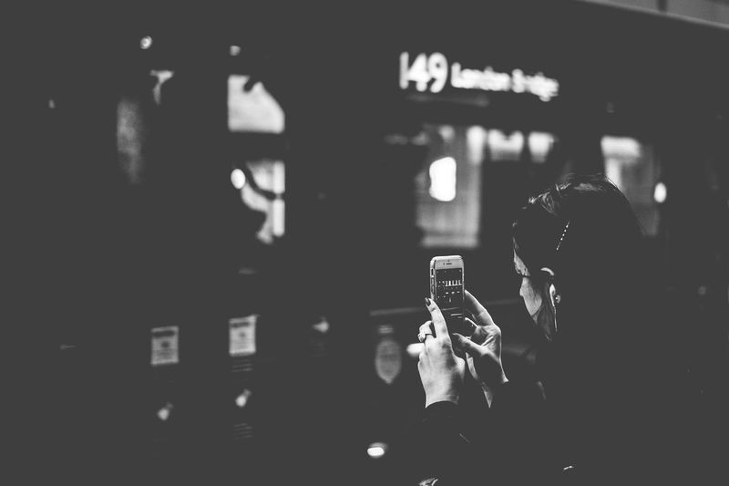 Rear view of man photographing through mobile phone at night