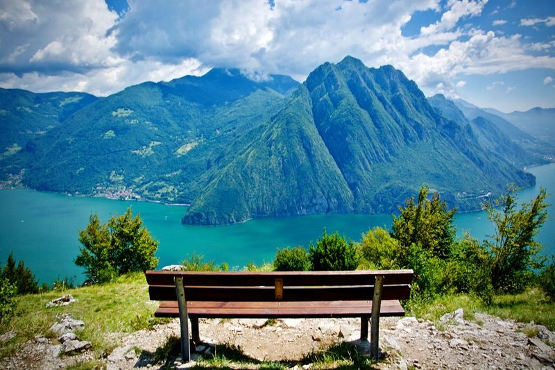 Empty bench by mountains against sky