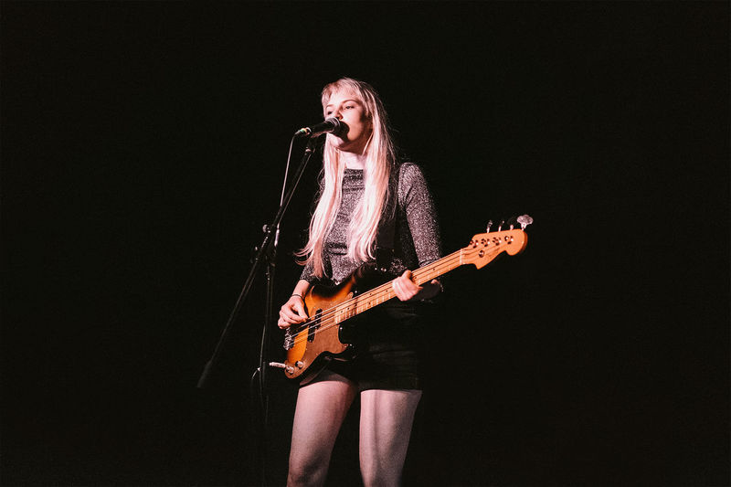 Young woman playing guitar against black background
