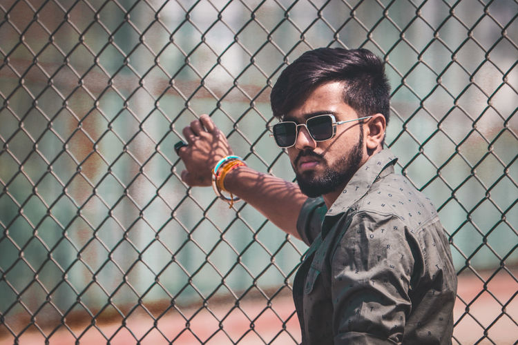 Portrait of young man wearing sunglasses on chainlink fence