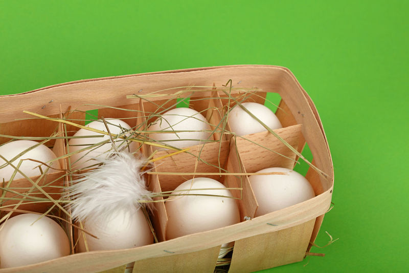 Close-Up Of Eggs In Crate Against Green Background