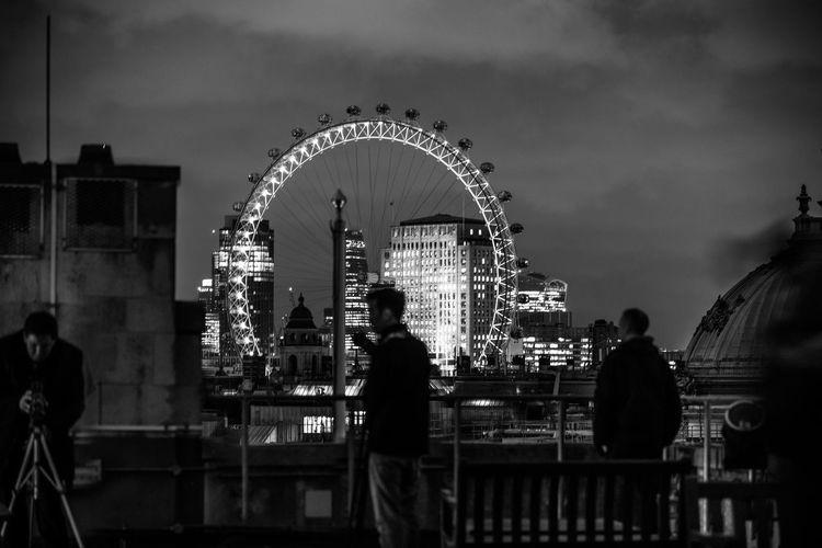 Men Standing On Bridge Against Millennium Wheel At Night