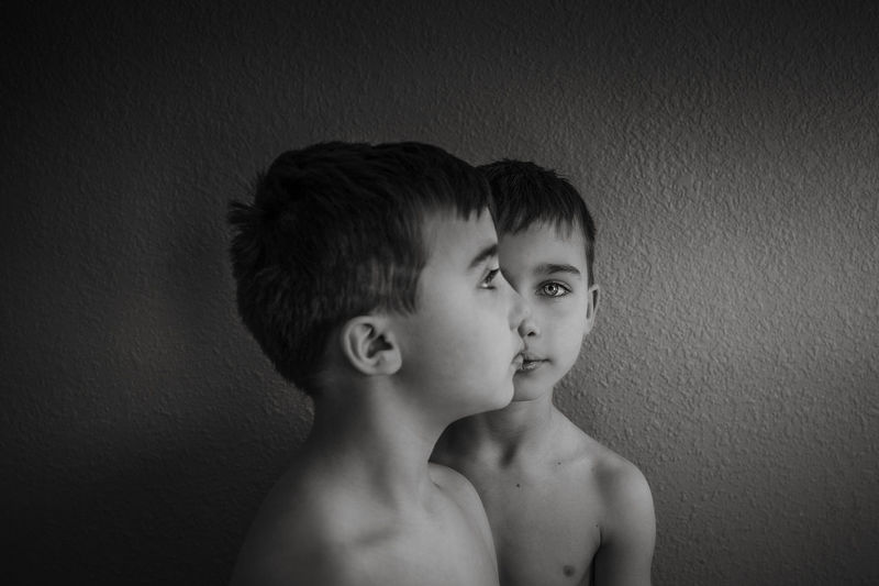 Portrait of shirtless boy against wall