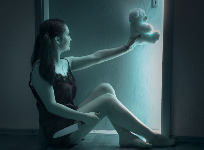 Side View Of Woman Holding Teddy Bear While Sitting By Door