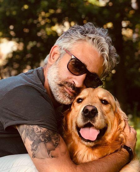 Portrait of man embracing dog