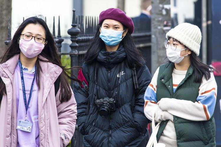 Portrait of friends standing on street in city