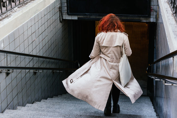 Rear view of woman with umbrella walking in city