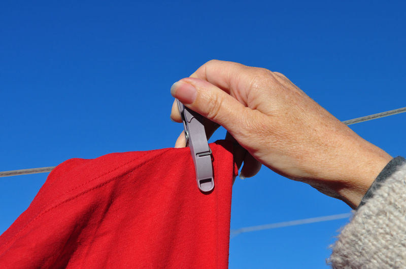 Close-up of hand holding red against blue sky