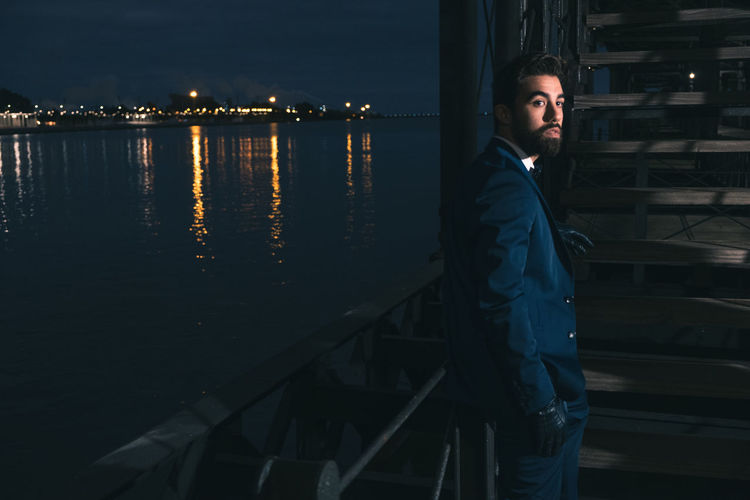 Side view of young man standing at railing on pier over river at night