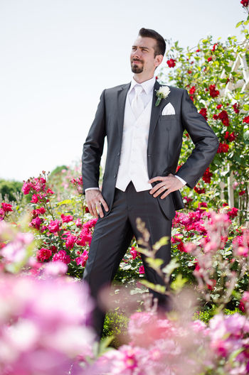 Bridegroom Standing Amidst Roses At Park