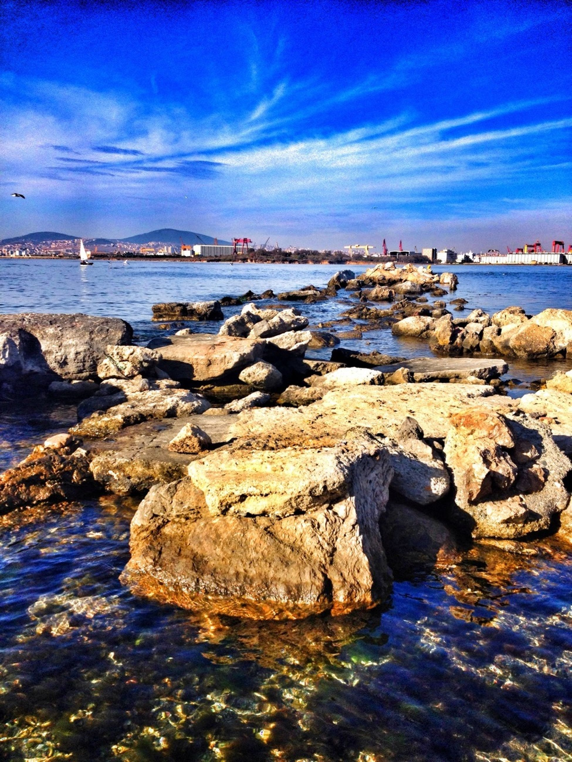 water, sea, sky, blue, tranquil scene, rock - object, tranquility, scenics, waterfront, beauty in nature, cloud - sky, beach, nature, cloud, rippled, shore, idyllic, outdoors, reflection, rock