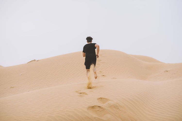Rear View Of Man On Sand Dune In Desert