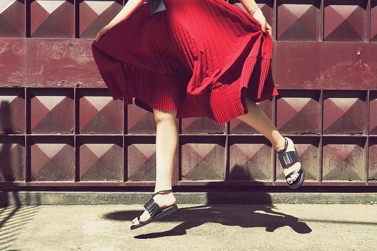 Low section of woman holding dress while jumping against metal gate