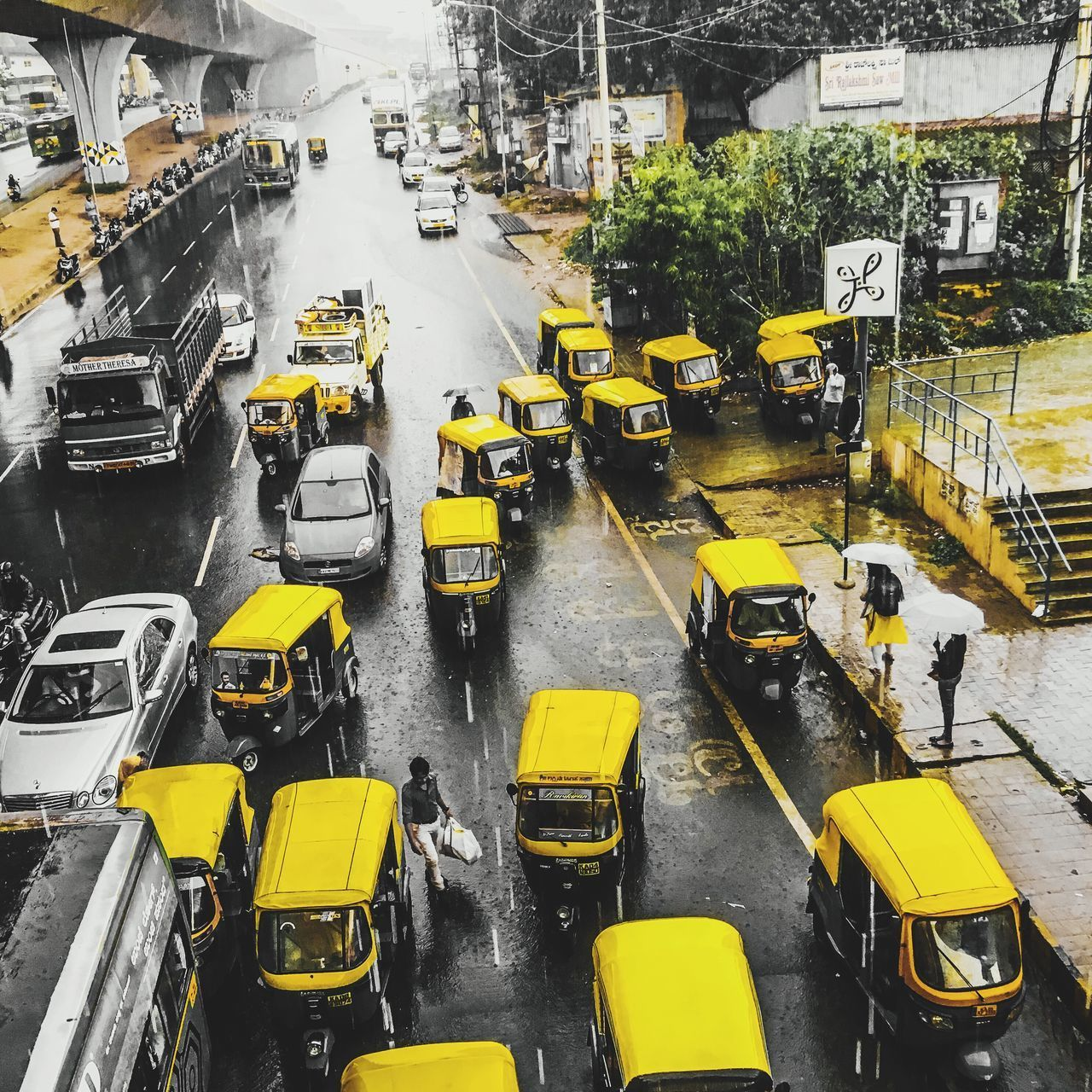 transportation, city, yellow, high angle view, architecture, mode of transportation, land vehicle, street, built structure, building exterior, motor vehicle, road, car, no people, city street, city life, traffic, outdoors, taxi