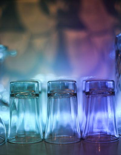 Close-Up Of Wineglasses Arranged On Illuminated Shelf In Bar