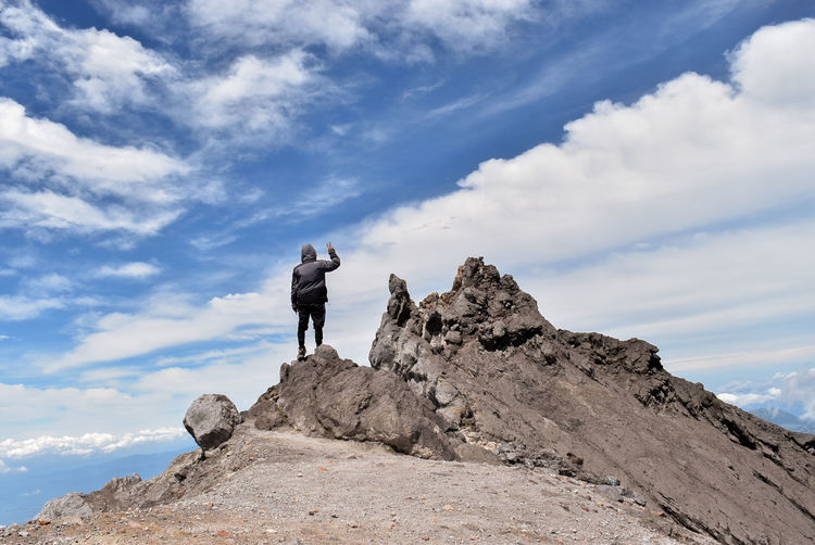 Rear view of hiker standing on rocky mountain against sky