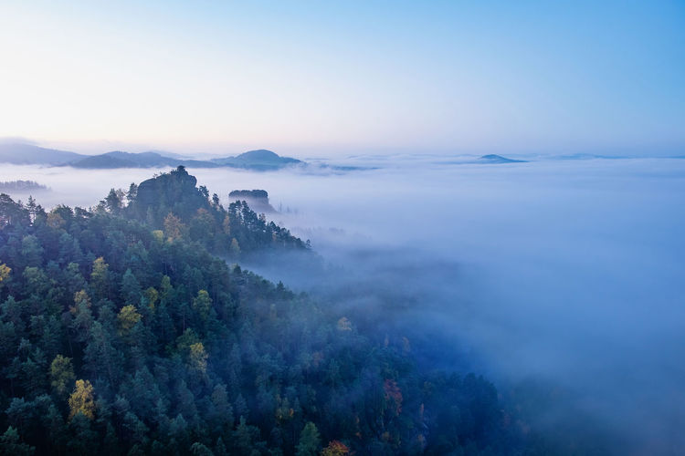 Mountain islands and misty valley, mountain peak with cabin at sunrise. beautiful autumn panorama