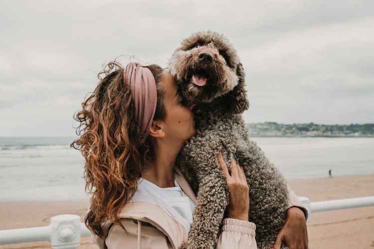 Woman kissing dog while standing at beach