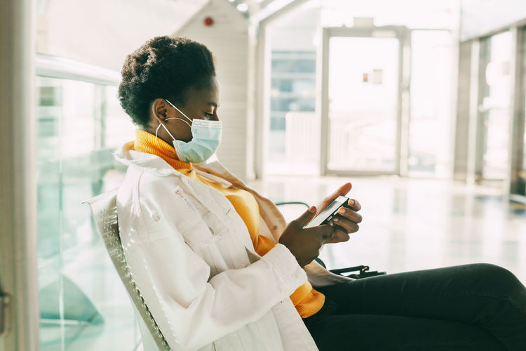 A young african woman in a protective mask sits in a chair in the waiting room