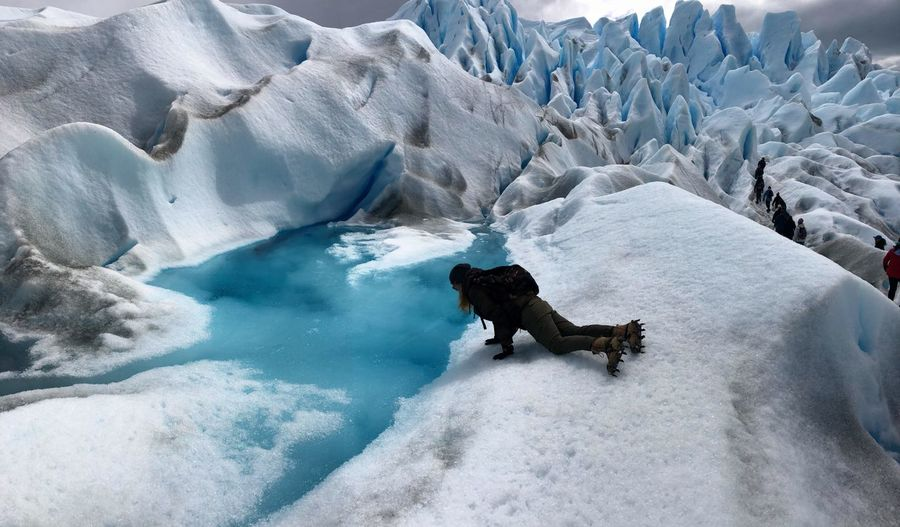 High angle view of woman lying by frozen lake