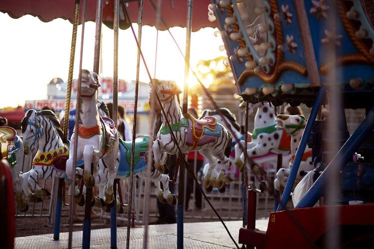 Carousel hanging in amusement park against sky