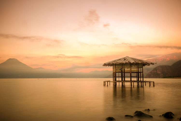Built Structure By Sea Against Sky During Sunset