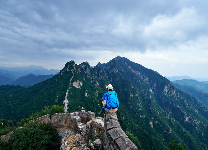 Man sitting against mountain on great wall of china
