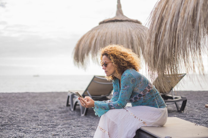 alternative office at the beach with ocean in background for a beautiful middle age woman working on her smartphone 40-44 Years Mobile Phone Casual Clothing Communication Connection Curly Hair Hairstyle Holding Leisure Activity Lifestyles One Person Outdoors Real People Sea Sitting Sky Straw Umbrellas Technology Tenerife Three Quarter Length Water Wireless Technology Young Adult Young Women