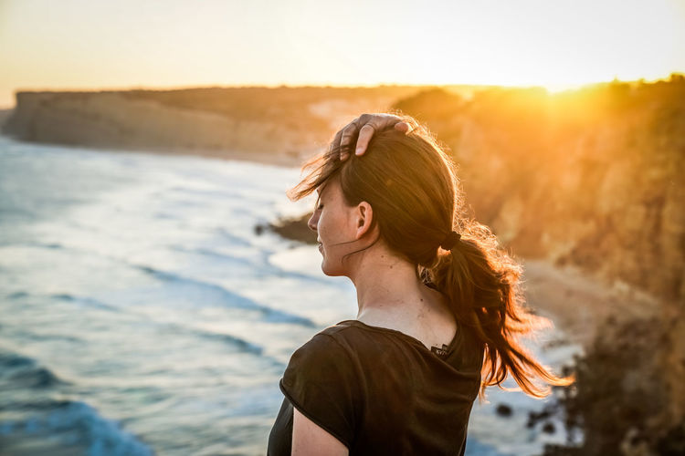 Young woman with hand in hair standing against seashore