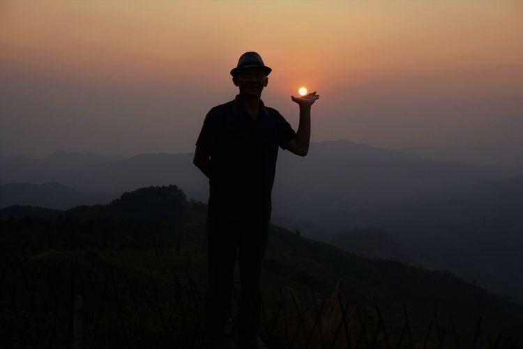 Optical illusion of silhouette man holding sun against sky during sunset