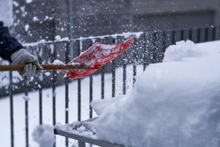 Unrecognizable person shoveling snow with an orange colored shovel
