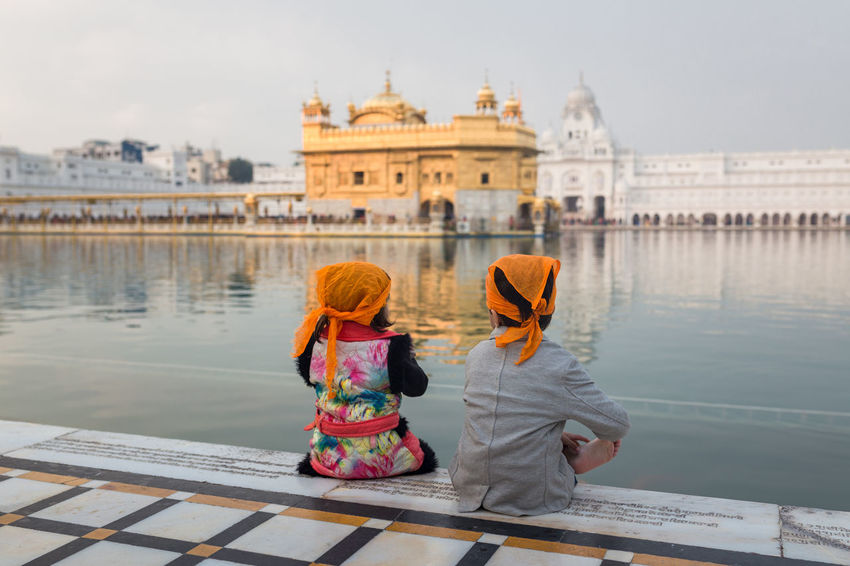 Two kids sitting in front of the Golden Temple, Amritsar, India Amritsar Boy Childhood Girl Golden Golden Temple Guru India Indian Kids Meditation Outdoors People Rear View Sahib Sikh Sikh Temple Sikhism Sitting Temple Togetherness Tourism Tourist Attraction  Travel Destinations Vacations