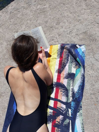 Rear view of woman reading book while lying on front at beach