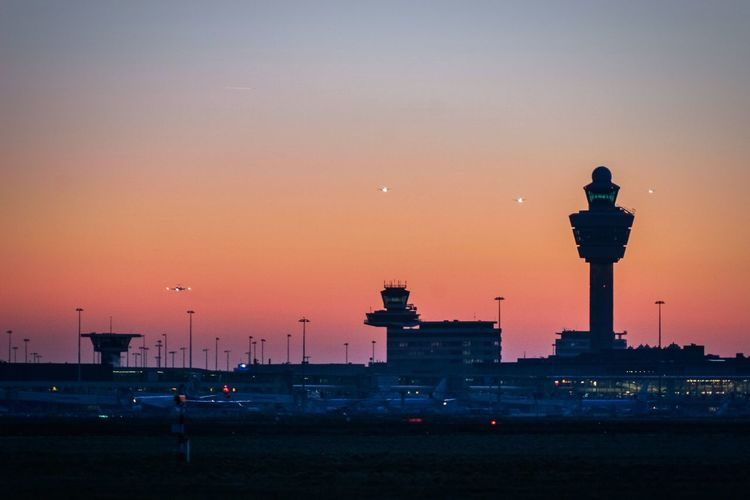 Air traffic control tower against sky during sunset at airport