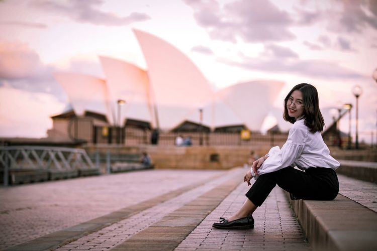 Sitting pretty 🌹 EyeEmNewHere Golden Hour Golden Hour Asian  Short Hair Operahouse Sydney Sunset Red Lipstick Portrait Photography Sydney Photography One Person Young Adult Women Sky Sitting Adult Young Women City Architecture Beauty Nature EyeEmNewHere