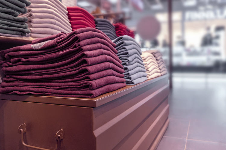Close-up of stack of clothing on table for sale in store