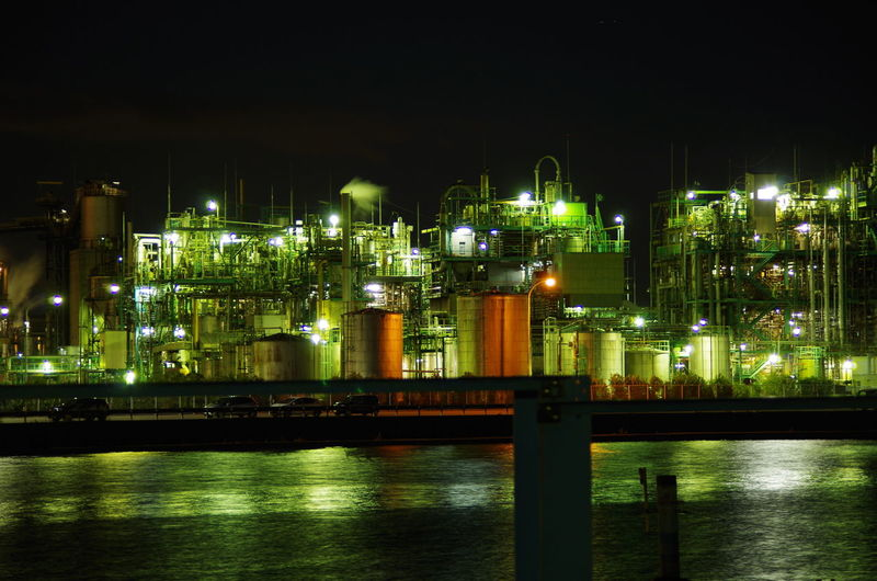 Illuminated factory by river against sky at night