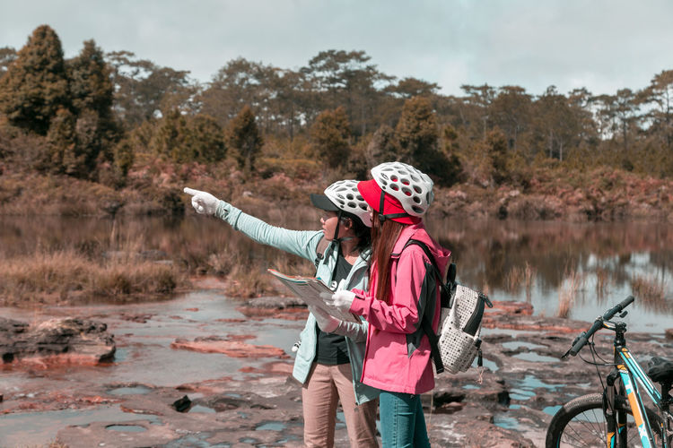 Two women travelling in Phu Kradueng Nation Park Thailand Water Nature Two People Women Leisure Activity Real People Lifestyles Standing Lake Tree Day Females People Togetherness Plant Casual Clothing Holding Adult Hat Outdoors Sister Maple Leaf Bycicle Travel Destinations Nature
