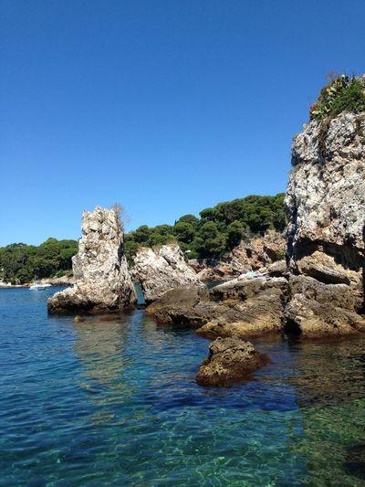 Rocks in sea against clear blue sky