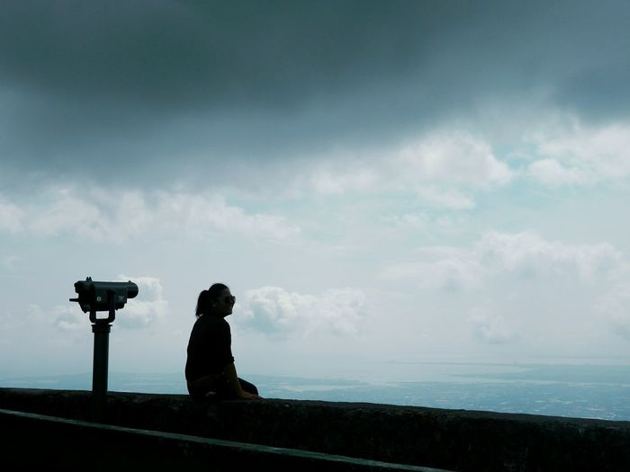 Silhouette Of Woman Sitting At Observation Point Against Cloudy Sky