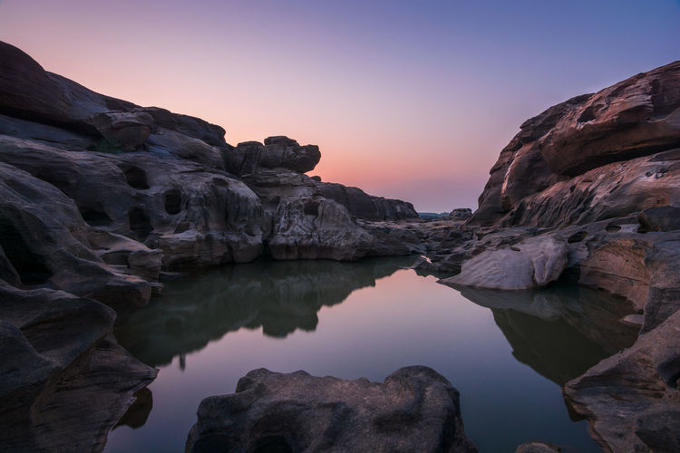 Rock formation in lake against sky during sunset