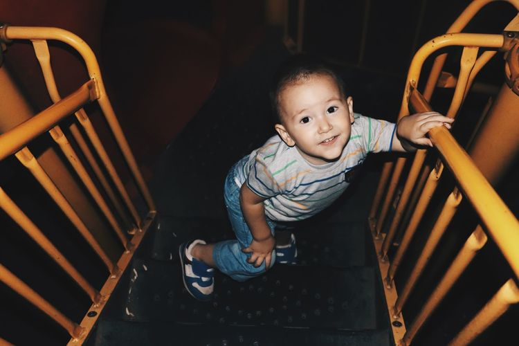 High angle portrait of cute boy standing on steps of slide at night