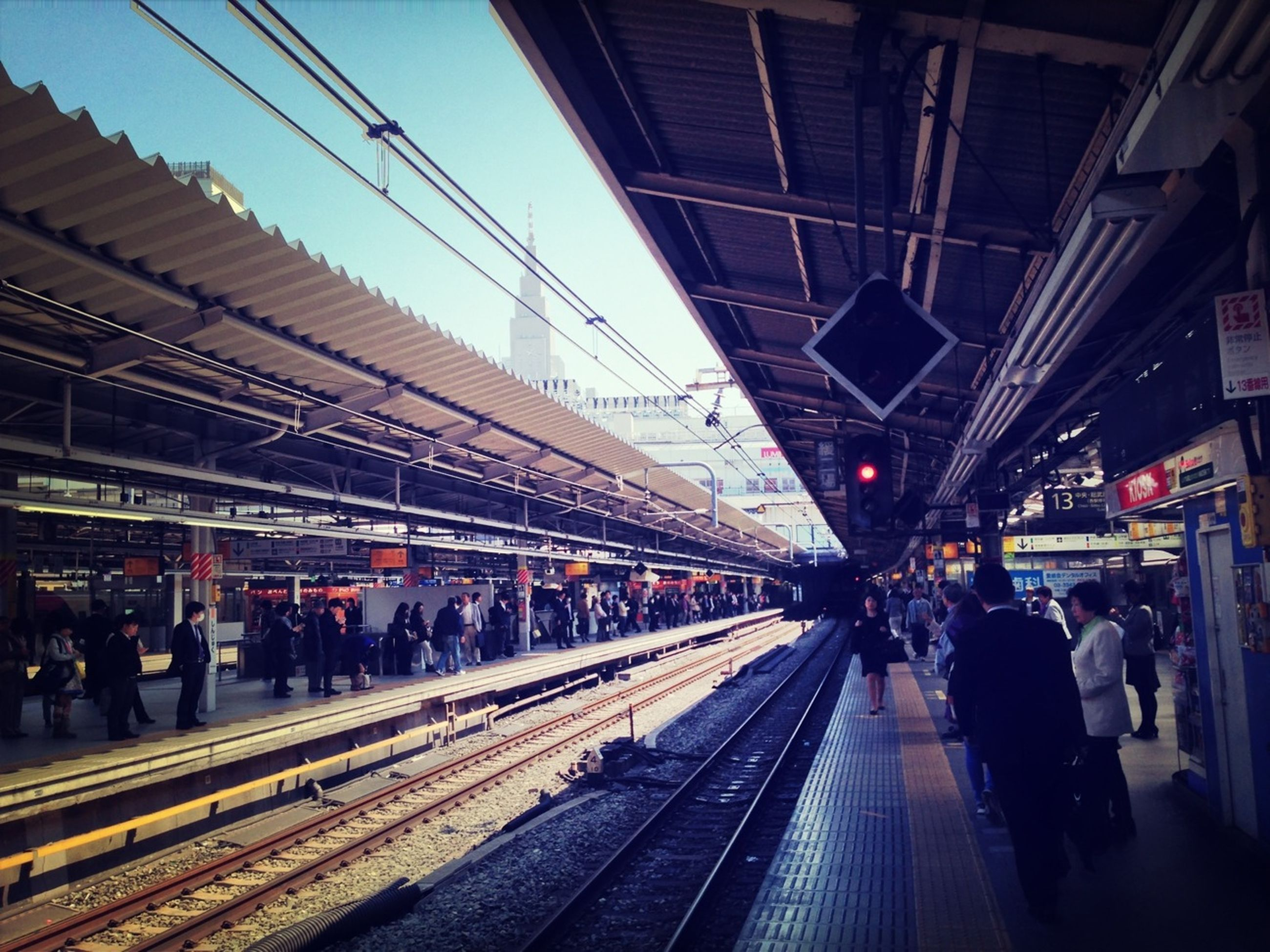 railroad station, large group of people, railroad track, railroad station platform, public transportation, rail transportation, transportation, indoors, person, illuminated, men, city life, built structure, lifestyles, architecture, ceiling, travel, passenger, transportation building - type of building