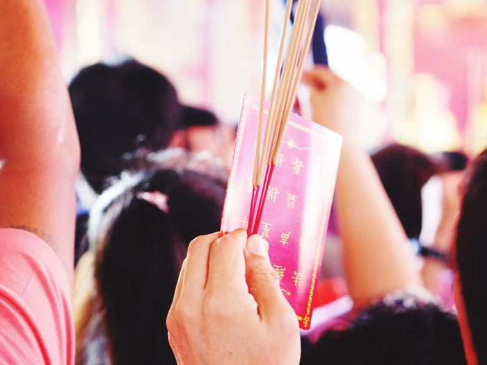Cropped Hand Holding Incense Sticks And Book At Temple