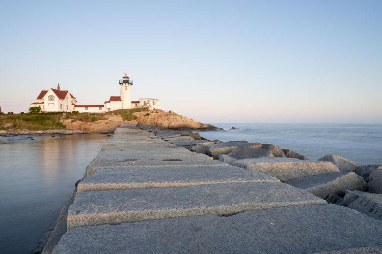 Lighthouse by sea against buildings against clear sky